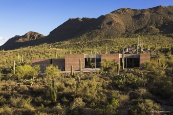 The  rammed earth home was designed to integrate with its desert landscape and mountain backdrop