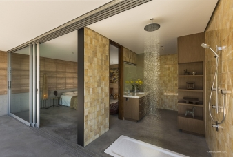 The bathroom with sunken bath, rainhead shower and tiled wall can be easily be opened to the bedroom and terrace