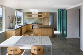 The kitchen features timber cabinetry and stainless steel benchtops