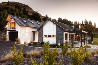 Rusticated Envira weatherboards are the perfect complement to schist on this classic New Zealand home design