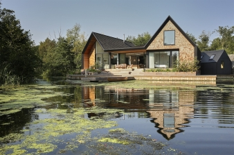 A new detached home designed by Platform 5 Architects replaces an outdated bungalow on a promontory in a secluded lagoon in the Norfolk broads, providing practice director, Patrick Michell with a family home