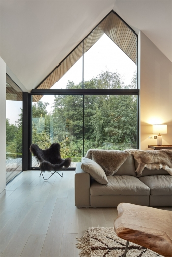 The double height vaulted living space faces onto woodland