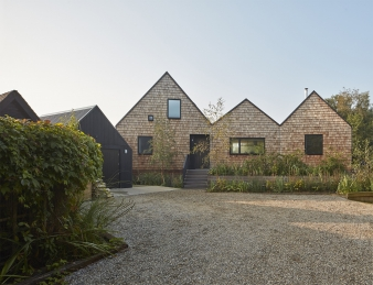 The house is arranged as three low rise bays, whose pitched roofs echo the working boat sheds typically found on the Broads