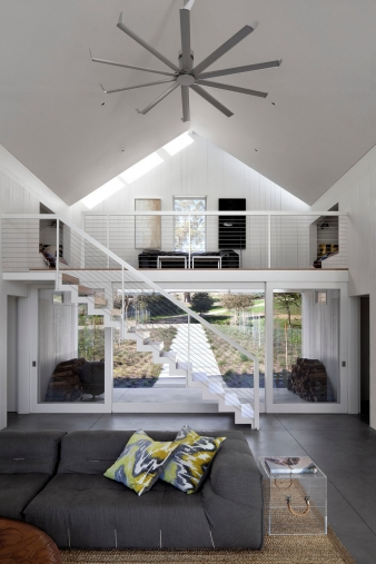 The entry provides shelter, tucked under the loft above, and frames a view through the house to the meadow beyond.