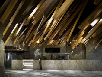 In the lobby of the Meteor Theatre, Guangzhou, long rectangular-cuboid decorations extend from the ceiling, mimicking the motion of a meteor shower streaking through the sky