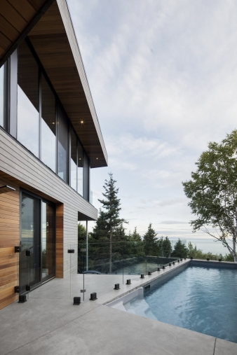 Terrace and pool beside the living room in new home by Bourgeois / Lechasseur architects