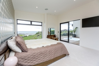 This bedroom in a Fowler Homes Taranaki design has access to a sheltered outdoor living space.