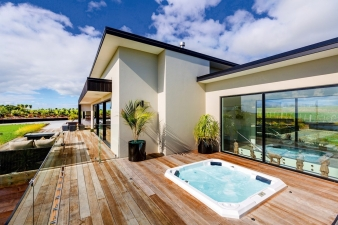 This expansive deck runs almost the length of the property – all part of a design by Fowler Homes Taranaki that connects to its scenic environment at every turn.