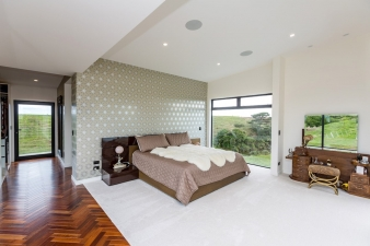 A feature wall and white surfaces are richly contrasted by a herringbone floor in this Fowler Homes Taranaki residence.