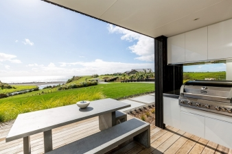 A sheltered outdoor barbecue area is a popular gathering point in this Fowlers Home Taranaki design.