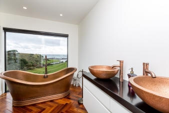A curvaceous freestanding tub is ideal for soaking up the scenery in this Fowler Homes Taranaki design.