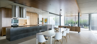 The dining and kitchen areas sit on a low raised terrace in a move that allows unobstructed views over the living area and out towards the park and river