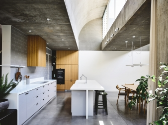 The kitchen's clean-lined design and sleek surfaces contrast with the raw texture of the structural concrete framework