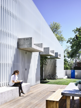 The entry sequence finishes in a recess, with raw concrete beams cantilevering out to provide partial shades and refuge, hanging plants from the gutter and grasscrete paving below