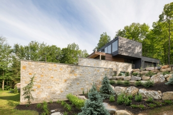 Lower levels of this new home are clad in stone, giving the impression that they project out of the landscape