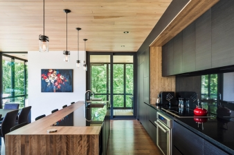 Kitchen and adjacent dining and living areas in a new home by Mu Architecture