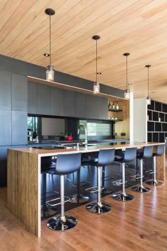 The black ash coloured kitchen and integrated furniture contrasts with the monochromatic whiteness of the walls