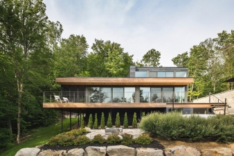 The massing of this house Mu Architecture and the use of natural stone and cedar create a tranquil composition in tis setting