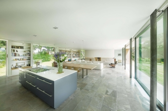 A large open-plan kitchen-dining-living area occupies the centre of the plan, with a covered terrace spanning its length and giving a sheltered outdoor area overlooking the Southern views