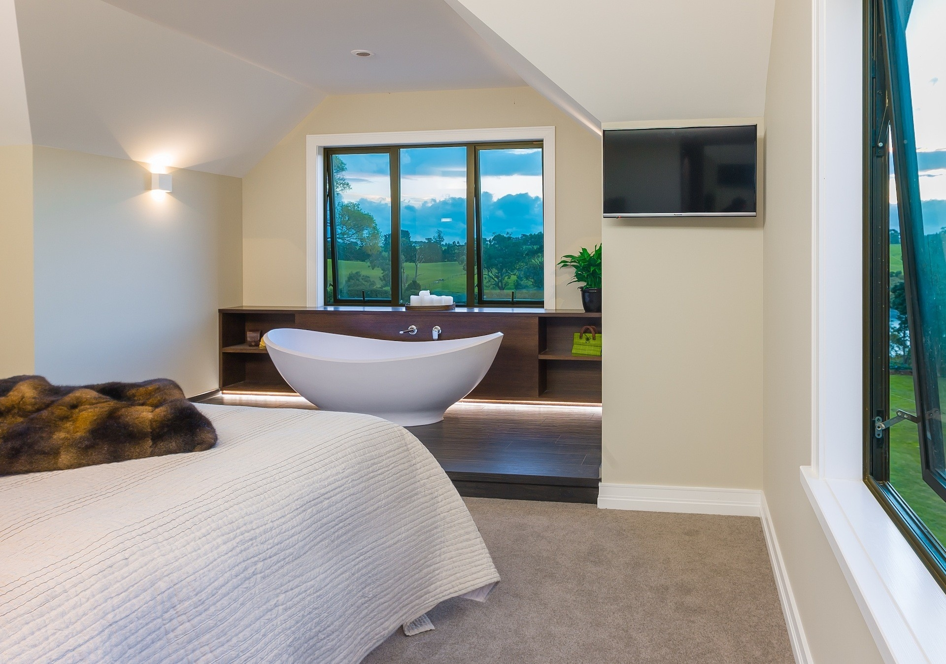 The design of this master suite takes  full advantage of the rural views  by placing a beautifully shaped freestanding bath central to the window, on a tiled plinth, at the foot of the bed