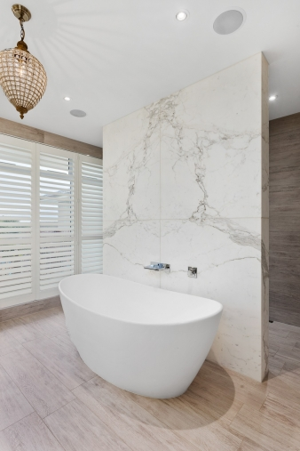 The walk-through shower is behind the statuary marble wall that acts as a backdrop for the freestanding bath tub