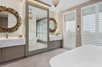 This  luxury bathroom by designer Mark Bruce boasts double vanities, in statuary vein marble, each have its own discreet storage. In addition, a generous cupboard is behind the full length mirror for  storage of towels etc
