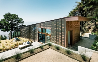 The south facade of this house is clad in copper which wraps up the wall and over on the roof. Copper clad roof overhangs protect windows and the front door from the sun and the wind of the ocean.
