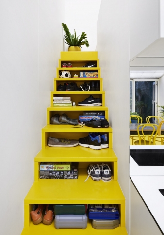 Bright yellow stairs with integrated storage in renovated terrace home