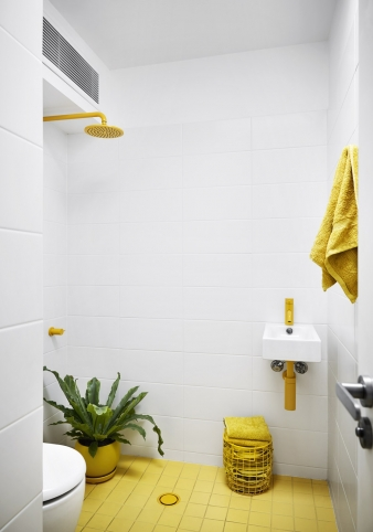 Small wet room with yellow showerhead