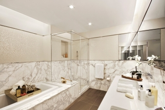 Master bathrooms at 738 Broadway are dressed in Calacatta marble and textured Porcelenosa Cubica tiles
