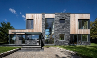 The residence is composed of two distinct two-storey volumes on either side of a double-height space containing the main entrance, a sculptural stair and a glass-floored footbridge on the second level.