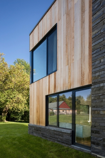 Echoing the old barn on the property, wooden cedar planks are employed as a secondary cladding on this rural home