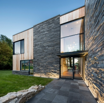 . As opposed to a typical natural stone cladding of thin slabs fixed to an exterior wall structure, the slate is cut into blocks of varying length and set in strata like bricks