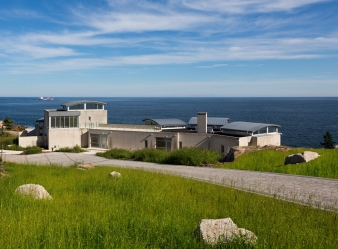 Crowned by gently curving zinc roofs, the pavilions in this home frames views of a historic lighthouse, the sea lanes to Halifax and a World War II Allied bunker