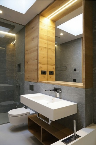The bathrooms are clad with natural stone and fitted out with oak furniture and Corian sanitaryware