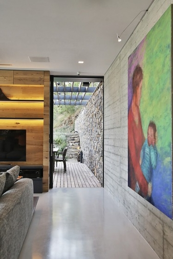 An exposed concrete wall to the back of the living room retains the imprint of the timber cast boards and functions as the feature art wall of the room.
