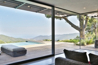 Large expanses of glass and sliding glass panels open the interior to the views
