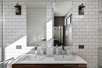 White tiles contrast with dark wood in one of the home's three bathrooms