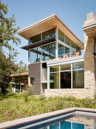 Building materials for this home include pre-weathered corrugated steel cladding, buff limestone walls, and large aluminum doors and windows