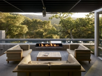 Outdoor living area with a firepit overlooks the pool in this new home