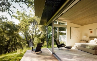 Guest suite opening to the outdoors through large sliding glass panels