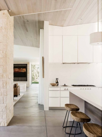 The interior palette of cedar-clad ceilings, oil-rubbed steel and exposed concrete floors soften the modern aesthetics into a refined but rugged ranch style in this new home