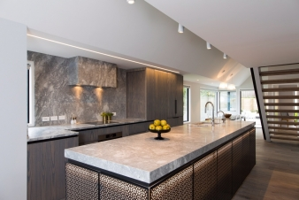 Granite features on the benchtops, splashback and rangehood cover in the new kitchen in this renovated home