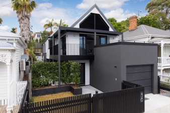 The house was reclad in rusticated cedar weatherboards, to complement  neighbouring turn-of-the-century villas, while a new monochromatic palette  helps  define the key architectural features