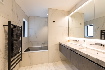 Large format tiles with a marble grain look add a touch of luxury to this master bathroom