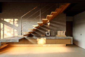 The floating staircase throws shadows across the wall