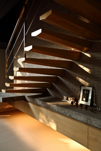 The staircase connects the two areas of the house while simultaneously providing a shelf